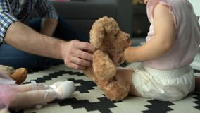 Little baby playing with soft bear at home stock video footage