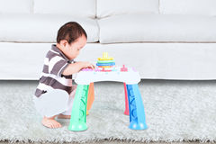 Little baby playing with toy. Little baby playing with colorful toy near the sofa in home Stock Photography