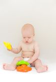 Little baby playing with toys. Over light gray background Royalty Free Stock Images