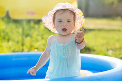 Little baby playing with toys in inflatable pool Royalty Free Stock Photo