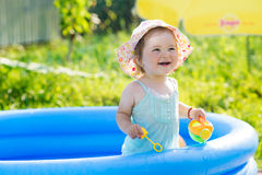Little baby playing with toys in inflatable pool Stock Photos