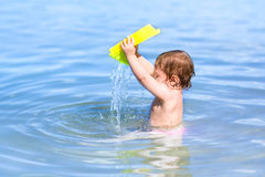 Little baby playing in the water on beach Stock Photo
