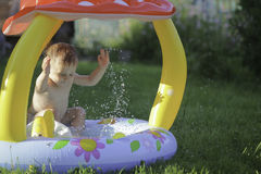 Little baby playing with water paddling pool in summer Royalty Free Stock Image