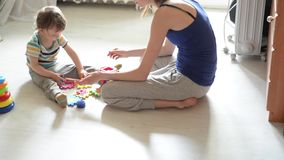 Little baby plays on the white floor with  mom stock footage