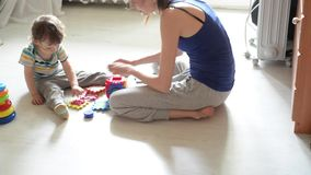 Little baby plays on the white floor with  mom stock video