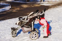 Little baby pushes his stroller in winter royalty free stock photos