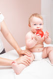 Little baby receiving osteopathic treatment of her leg. Seven month baby girls knee joint being manipulated by osteopathic manual therapist or physician Stock Photo