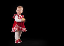 Little baby in red dress with apple Stock Photos