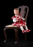 Little baby in red dress on the armchair Royalty Free Stock Photography
