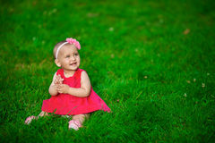 A little baby in a red dress sits on a grass. A little baby in a red dress sits on a green grass Royalty Free Stock Photography