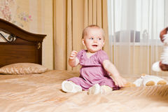 Little baby in red dress sitting on the floor Royalty Free Stock Images