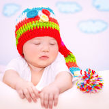 Little baby relaxing at home. Portrait of cute sweet baby girl with closed eyes relaxing on the couch at home, wearing funny colorful knitted hat Royalty Free Stock Image