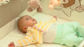 Little baby is resting in his crib Stock Photos