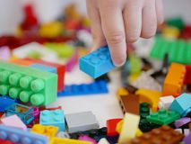 Little baby`s hand picking / choosing a piece of colorful interlocking plastic bricks royalty free stock images