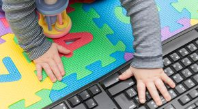 Little baby`s hands, on a computer mouse and keyboard - child development, getting familiar with technology since their early age stock photo