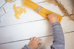 Little baby`s hands holding pasta on the white wooden table, cooking with children concept stock image