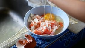Little baby`s hands learning to crack an egg to make crab stick omelette at home.  stock video footage