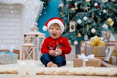 Little baby santa claus in christmas hat. Happy new year and merry christmas. Holidays and gifts for children.  stock photos