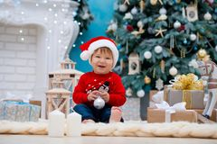 Little baby santa claus in christmas hat. Happy new year and merry christmas. Holidays and gifts for children.  stock image