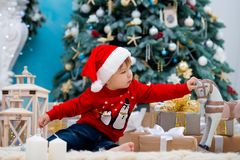 Little baby santa claus in christmas hat. Happy new year and merry christmas. Holidays and gifts for children.  stock photo