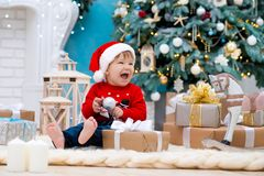 Little baby santa claus in christmas hat. Happy new year and merry christmas. Holidays and gifts for children.  stock images