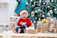 Little baby santa claus in christmas hat. Happy new year and merry christmas. Holidays and gifts for children.  royalty free stock photo