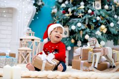 Little baby santa claus in christmas hat. Happy new year and merry christmas. Holidays and gifts for children.  royalty free stock image
