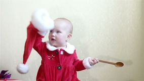 Little baby in santa suit holding a spoon. stock footage
