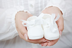 Little baby shoes. Closeup picture of new baby shoes in expectant mother's hands Stock Photos