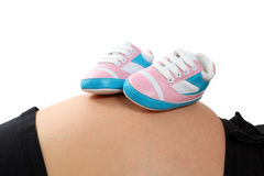 Little baby shoes. On pregnant belly Stock Images