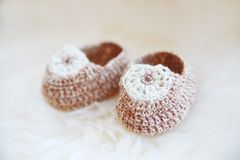 Little baby shoes. Hand knitted first bootees for newborn  girl. Royalty Free Stock Image