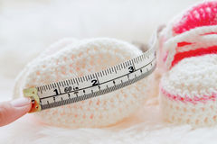 Little baby shoes. Hand knitted first sneakers for newborn  girl Stock Photo