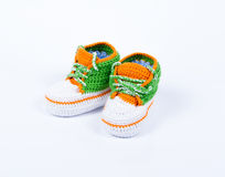 Little baby shoes. Hand knitted sneakers for newborn boy or girl. Crochet handmade bootees on white background Stock Photo