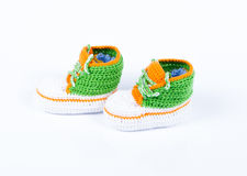 Little baby shoes. Hand knitted sneakers for newborn boy or girl. Crochet handmade bootees on white background Stock Photography