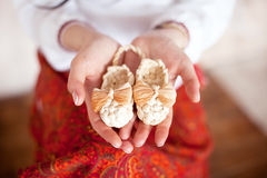 Little baby shoes on the palms of the mother. Royalty Free Stock Image