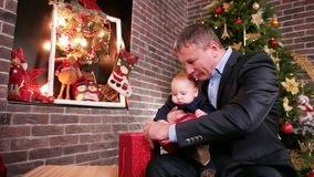 Little baby sitting on the arms of his father, male playing with his small, sweet son good father spends Christmas Eve stock video footage