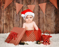 Little Baby Sitting in Christmas Present. A little baby is wearing a Christmas santa hat and sitting in a present with a wood backdrop for a season or portrait royalty free stock image