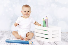 Little baby sitting on the floor with big coloring pencils Royalty Free Stock Photo