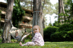 Little baby sitting on the grass. While staying at tropical hotel Stock Image