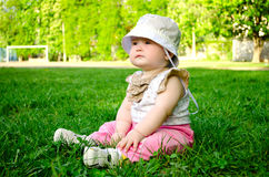 Little baby sitting on the green grass. Small beautiful baby sitting on green grass and looking to the side stock photography