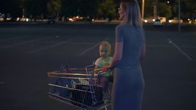 Little baby sitting in a grocery cart, while her mother is pushing the cart forward walking at the parking place by the stock video