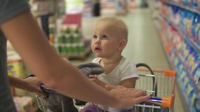 Little baby sitting in a grocery cart in a supermarket holding a toy, while her mother is pushing the cart walking among stock video