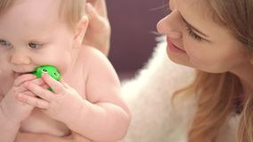 Little baby sitting in mother embrace. Baby in diapers eating green toy. Portrait of little kid playing with toy frog. Tenderness parenthood. Close up of naked stock footage