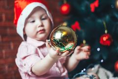 Happy baby in Santa s hat hiding behind a ball against Christmas tree with decorations. Ball in focuse. Baby unfocused. Stock Photography