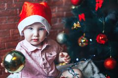 Happy baby in Santa s hat hiding behind a ball against Christmas tree with decorations. Ball in focuse. Baby unfocused. Royalty Free Stock Photos