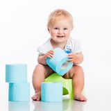 Little baby sitting on a pot. And keeps the toilet paper. studio photo on white royalty free stock image