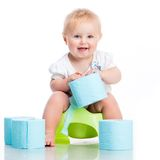 Little baby sitting on a pot. And keeps the toilet paper. studio photo on white background royalty free stock photos
