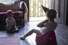 Little baby sitting on a potty. With party hat on the cottage with his younger sister royalty free stock images