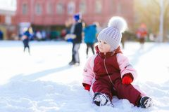 Little baby is sitting on the snow at sunset. Little kid plays in the street in winter Stock Photos
