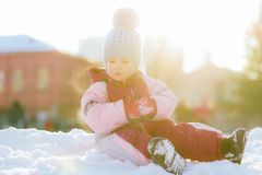 Little baby is sitting on the snow at sunset. Little kid plays in the street in winter Stock Photography